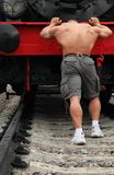 Strong shirtless man pushs locomotive Royalty Free Stock Image