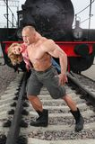 Strong shirtless man saving girl on railroad Stock Image