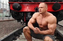 Strong shirtless man sits against locomotive Royalty Free Stock Image