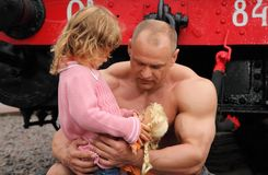 Strong shirtless man sits with little girl Stock Photos