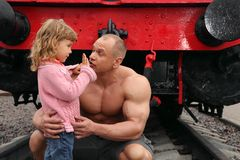 Strong shirtless man sits on railroad with girl Royalty Free Stock Photo
