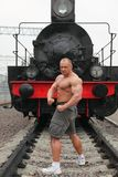 Strong shirtless man stands against locomotive Stock Photography