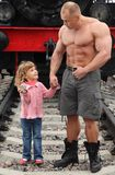 Strong shirtless man stands on railroad with girl Royalty Free Stock Photos