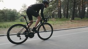 Strong skinny fit cyclist riding a bicycle in the park. High speed cycling uphill out of the saddle. Side follow view. Cycling con. Cept stock video footage