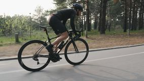 Strong skinny fit cyclist riding a bicycle in the park. High speed cycling uphill out of the saddle. Side follow view. Cycling con. Cept. Slow motion stock footage