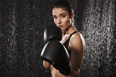 Strong slim woman boxing wearing gloves and standing in defense. Position under rain drops isolated over black background stock photography