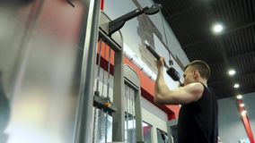 Strong slim young man professional bodybuilder engaged with arm and back muscle. Strong young man professional bodybuilder engaged with arm and back muscle stock video footage