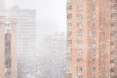 Strong snowing and apartment houses in winter Stock Photos
