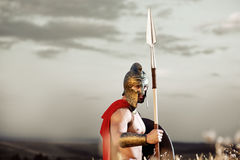 Strong Spartan warrior in battle dress with a shield and a spear royalty free stock images