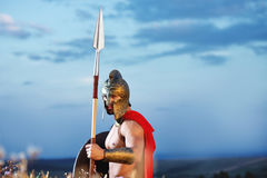 Strong Spartan warrior in battle dress with a shield and a spear. Lonely fighter. Legionary warrior in a helmet and battledress standing alone holding a shield Royalty Free Stock Photo