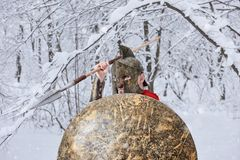 Strong spartan warrior is waiting for danger in snowy forest. royalty free stock photo
