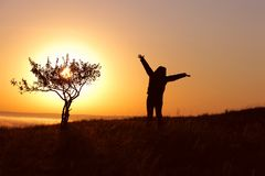 Strong girl standing facing the sun Royalty Free Stock Photo