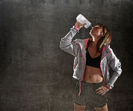 Strong sport freckles woman drinking water after training workout  in gym club harsh light Royalty Free Stock Photography