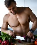 Strong sport man ready to cook cut beetroot vegetables on kitchen background healthy eating concept. On black background Stock Images