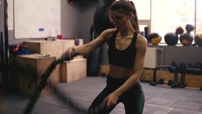 Strong sportive brunette girl in her 20`s performing battle ropes workout at the gym. Strong sportive brunette girl in her 20`s performing battle ropes workout stock footage