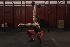 Strong sports woman doing dumbbell squats. Crossfit female athlete lifting weights royalty free stock photos