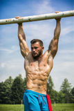 Strong sportsman doing abs exercise outdoor. Portrait of tattooed topless sportsman doing abs exercise on metal railing outdoor in city park Stock Photo