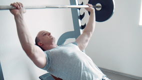 Strong sportsman doing biceps curls with barbell