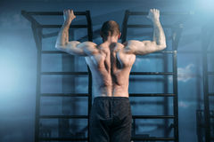 Strong sportsman training on horizontal bar in gym. Back view. Muscle athlete on workout Stock Photography
