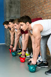 Strong sportsmen exercising with weights Royalty Free Stock Image