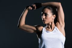 Strong sportswoman showing muscular biceps. Isolated on grey stock image