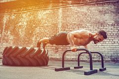 Strong sporty happy cheerful positive man doing press exercises holding plank outdoors stock images