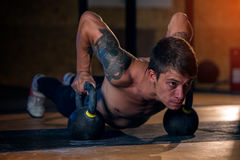 Strong sporty man doing push up with kettle bell royalty free stock photo