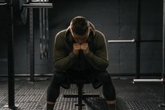 Strong sporty man sitting on gym bench suffering breakdown to overcome stock image
