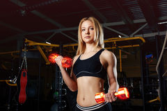 Strong sporty woman bodybuilder with tanned body doing exercises with dumbbell in the gym. Sports and fitness. Fiery dumbbells. Royalty Free Stock Photo