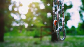 A strong steel chain with large links hangs down against the background of nature