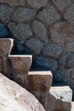 Strong stone steps. Strong handmade stone steps staircase, and stone wall, frontal view in hard sun light royalty free stock image