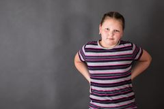 Strong stout girl with arms akimbo. On a grey background stock image
