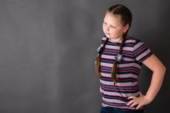 Strong stout girl with arms akimbo. On a grey background royalty free stock photos
