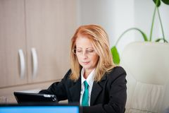 Strong successful business woman in a meeting at the office. Mature thinking stock image