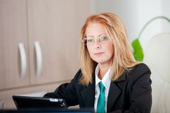 Strong successful business woman in a meeting at the office. Mature thinking royalty free stock image