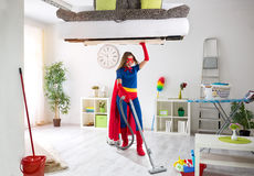Strong super housewife cleaning home and holding bad in the air Stock Image