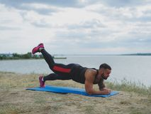 A strong tattooed bodybuilder standing in a plank on a bank of a river on a blurred natural background. Stock Image