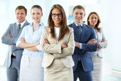 Strong team. Confident business team with a female leader looking at camera and smiling Royalty Free Stock Image