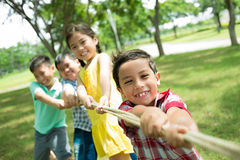 Strong team. Team of four kids pulling the rope in the tug-of-war game Stock Photo