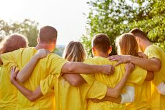 Strong team at a team building event. Young strong team hugs each other at a team building event in nature stock images