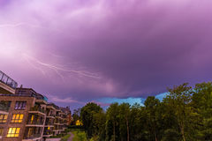Strong thunderbolt in purple stormy sky over modern houses at night.  stock photography
