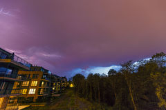 Strong thunderbolt in purple stormy sky over modern houses at night.  royalty free stock images