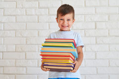 Strong toothy smiling little boy holding a big pile of books. Standing against white wall Royalty Free Stock Images