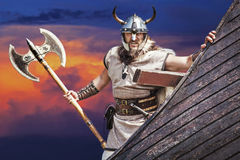 Strong Viking on his ship. Angry man holding historical axe weapon on ship looking at camera stock photography