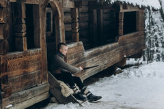 Strong viking warrior sharpening his sword while sitting near an. Cient wooden castle, scandinavian knight with weapon in viking costume, historical heritage stock photography