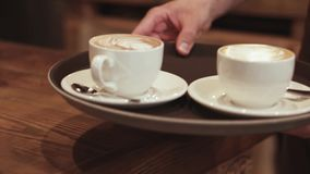 A strong waiters hand carries a brown tray with coffee espresso in two white cups to the customers. Modern cafe. Morning stock footage