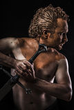 Strong warrior licking a sword, covered in mud and naked. Strong warrior licking a sword, covered in mud Royalty Free Stock Photos