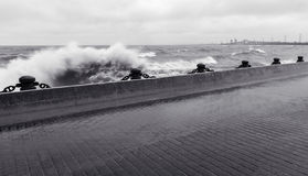 Strong wave crashing against pier at waterfront in stormy weathe Stock Photography