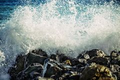 Strong wave of  sea beats on the rocks stock photography