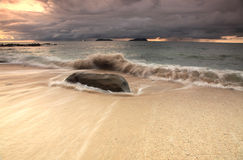 Strong waves and big rock on the beach. Royalty Free Stock Image